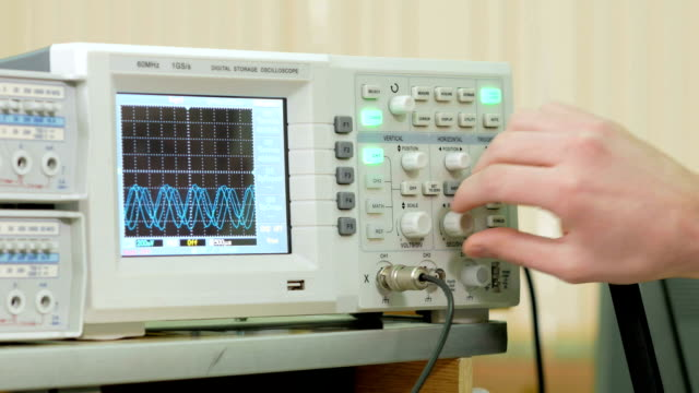 Men's engineering arm adjusts the oscilloscope for proper display of the electrical signal. Modern small industrial oscilloscope video