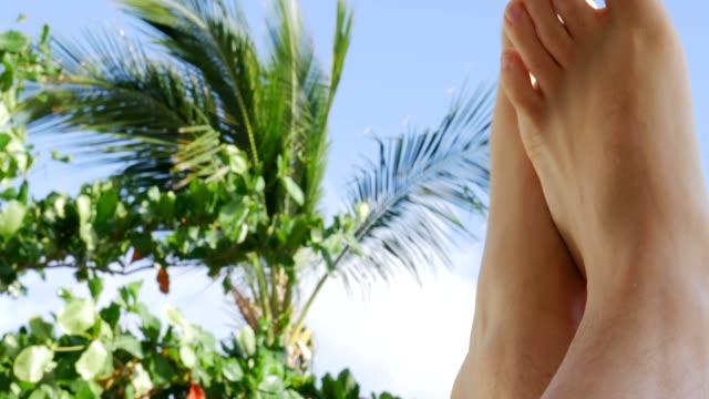 Men's feet relaxing on the beach, POV