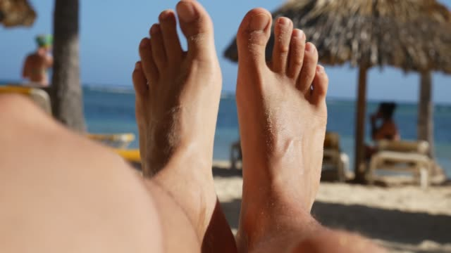 Men's feet relaxing on the beach, POV Men's feet relaxing on the beach, POV sunbathing stock videos & royalty-free footage