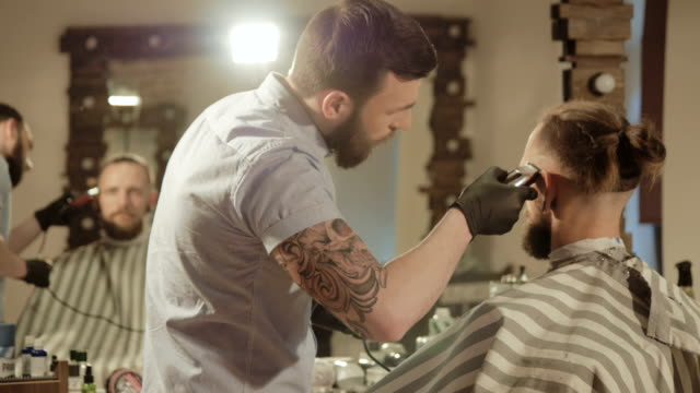 men's hairstyling and haircutting with hair clipper in a barber shop or hair salon video