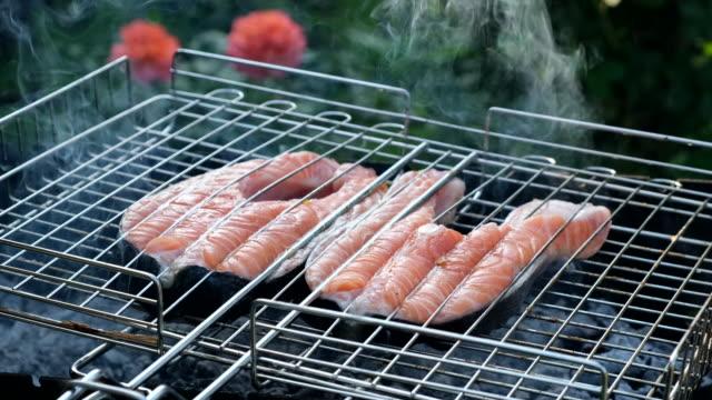 mäns hand vända fisk i gallret på grillen. village livsstil. lax rödfisk på en grill. grillning öring biffar. matlagning rostad fisk på öppen eld - marinad bildbanksvideor och videomaterial från bakom kulisserna