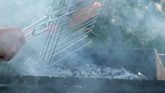 mäns hand vända fisk i gallret på grillen. village livsstil. lax rödfisk på en grill. grillning öring biffar. matlagning rostad fisk på öppen eld. grill, utomhus - marinad bildbanksvideor och videomaterial från bakom kulisserna