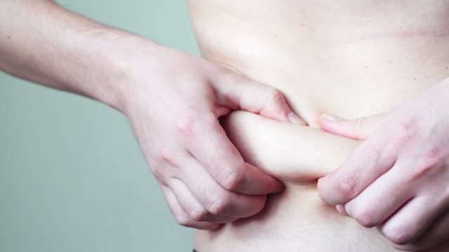 men's hands check a layer of fat on the sides and stomach, close-up. the problematic friable body of a young man requires exercise stress and training slowmo - cięcie w linii środkowej filmów i materiałów b-roll