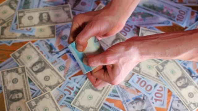 vídeos y material grabado en eventos de stock de las manos de los hombres cuentan billetes de 20 euros. antecedentes hechos de dólares. - accesorio financiero