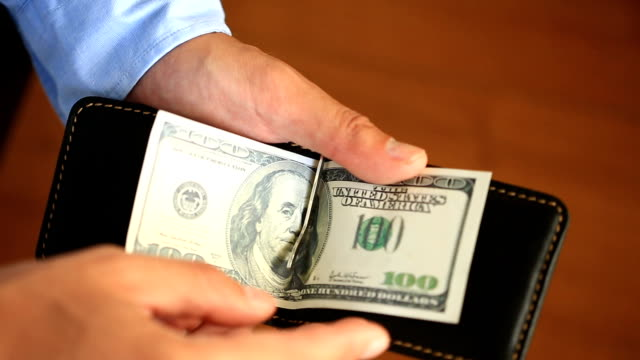 Men's hands hold a money clip with dollars video