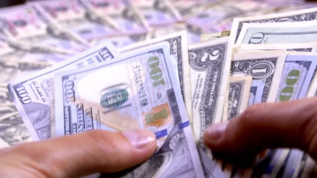 men's hands hold a pile of american dollars against the background of rotating money - gioco d'azzardo video stock e b–roll