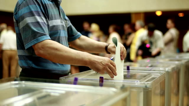 Men's hands put the electoral billeting in the ballot box