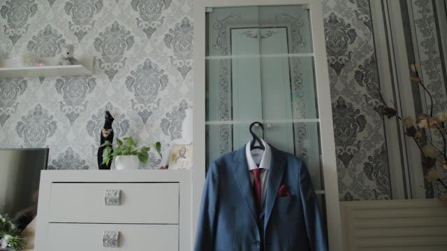 men's jacket hanging on a closet - жакет стоковые видео и кадры b-roll