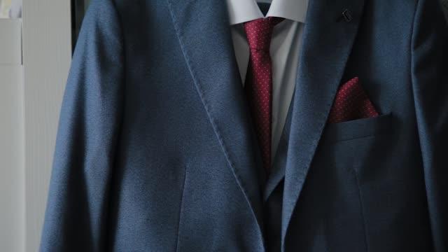 vídeos y material grabado en eventos de stock de chaqueta de hombre colgando en un armario - corbata