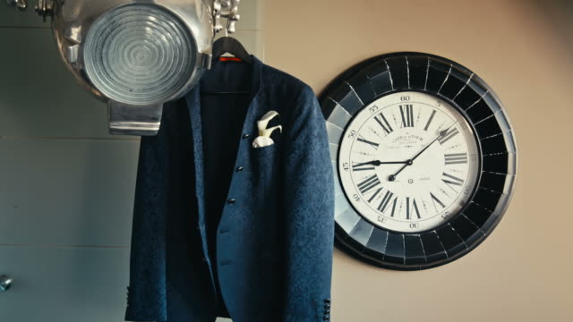 men's jacket hanging on the floodlight near the clock video