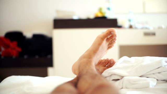 men's legs on bed in bedroom - dito del piede video stock e b–roll