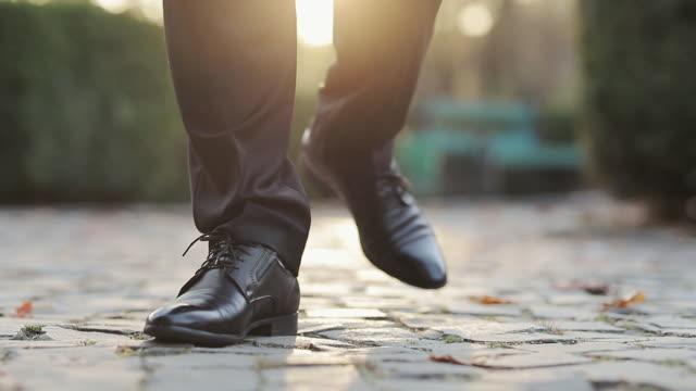mäns stil. man i svarta skor kliva framåt person flyttar framåt utomhus. närbild på människans läderskor. närbild av lyxskor, affärsman walking, elegant rik person. - formell klädsel bildbanksvideor och videomaterial från bakom kulisserna