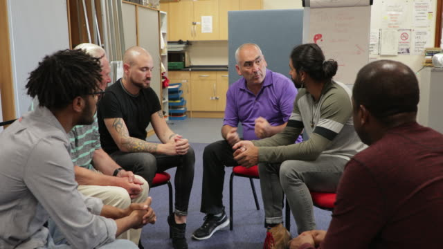 Men's Volunteer Support Group Diverse group of men are talking to a mental health professional in a support group meeting. sociology stock videos & royalty-free footage