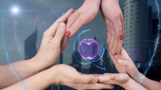 Men's, women's and children's hands show a hologram 3d apple