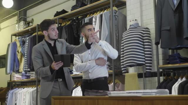 erkek giyim mağazası çalışanı ve müşteri dijital tablette ürünlere bakıyor - i̇yi giyimli stok videoları ve detay görüntü çekimi