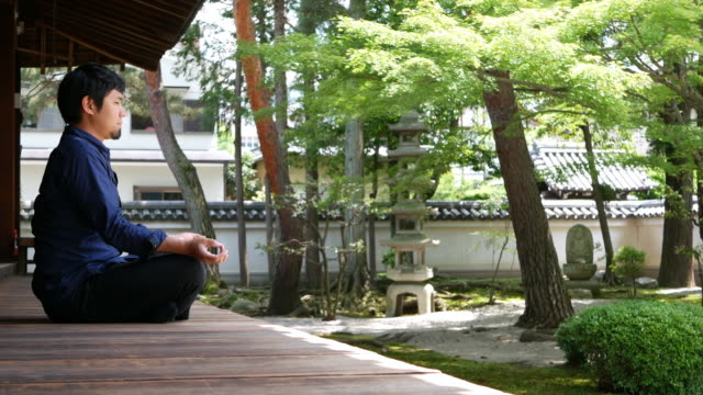 Mental balance and meditation A man sitting at the garden of a buddhist temple, meditating. cross legged stock videos & royalty-free footage