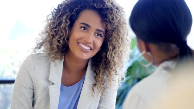 Mental health professional advises female patient Beautiful mixed race female mental health professional smiles while giving advice and encouragement to unrecognizable young female patient. The doctor gestures while speaking positively to the patient. mental wellbeing stock videos & royalty-free footage