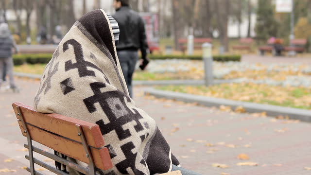Mentally ill person hiding under blanket, happy people walking in autumn park video