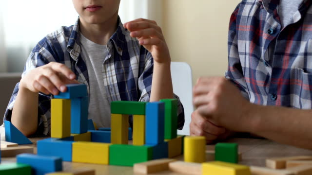 Mentally retarded teenager playing with cubes, volunteer looking after him Mentally retarded teenager playing with cubes, volunteer looking after him autism stock videos & royalty-free footage