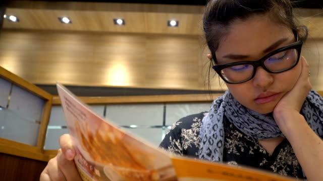 Menu The Asian woman looking menu in the restaurant. menu stock videos & royalty-free footage