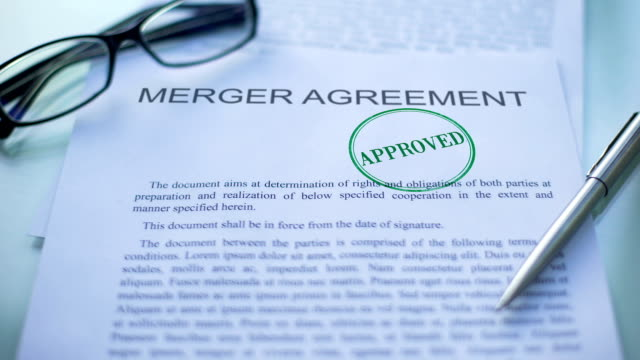 Merger agreement approved, officials hand stamping seal on business document
