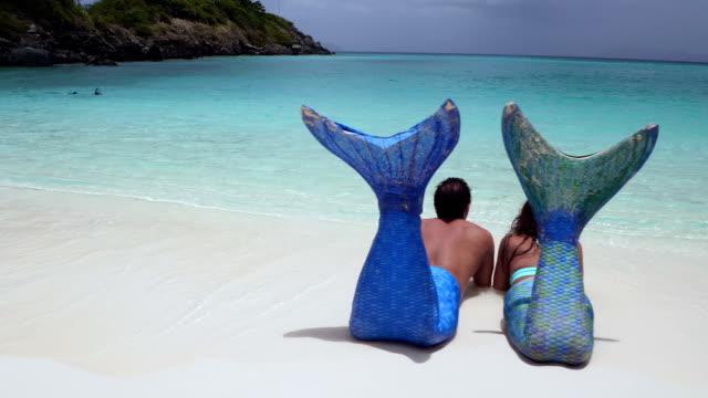 mermaid couple relaxing on tropical beach