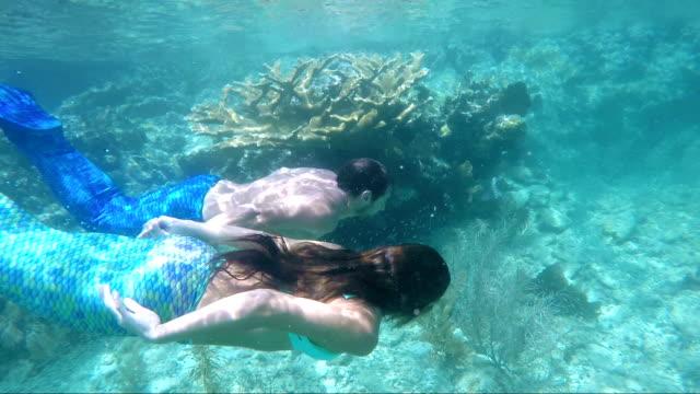 mermaid couple swimming underwater from tropical beach