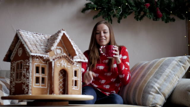 merry christmas and happy holidays. young woman are drinking warm tea with christmas cookies - happy holidays stock videos & royalty-free footage