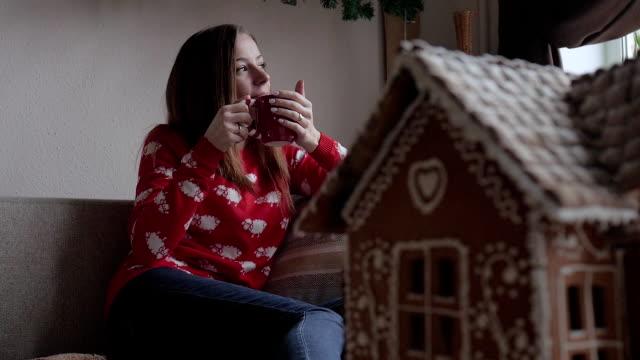 frohe weihnachten und schöne feiertage. junge frau trinken warmen tee mit weihnachtsgebäck - lebkuchenhaus stock-videos und b-roll-filmmaterial