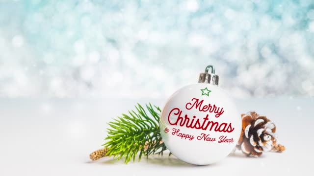 merry Christmas and happy new year on white Christmas glossy ball on white table at sparkling blue bokeh blur abstract background,Holiday greeting seasonal
