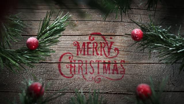 sfondo natalizio allegro, movimento della telecamera, neve che cade, vecchia parete di legno, rami innevati con decorazioni regalo e stelle - christmas table video stock e b–roll