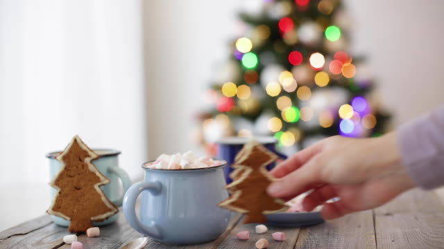 Merry Christmas! Christmas tree-shaped gingerbread cookie near cups of cocoa and marshmallows. Beautiful blurred christmas tree background with luminous garland.
