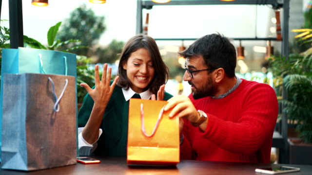 Merry Christmas my love. Closeup side view of a mid 20's couple exchanging Christmas gifts with each other. She just got what she's been hoping for and seems very happy and cheerful. market retail space stock videos & royalty-free footage