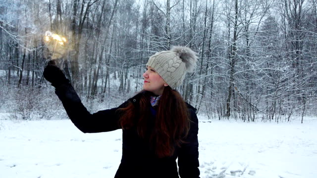 Merry girl hold burning sparkler stick, show it to camera, slow motion video