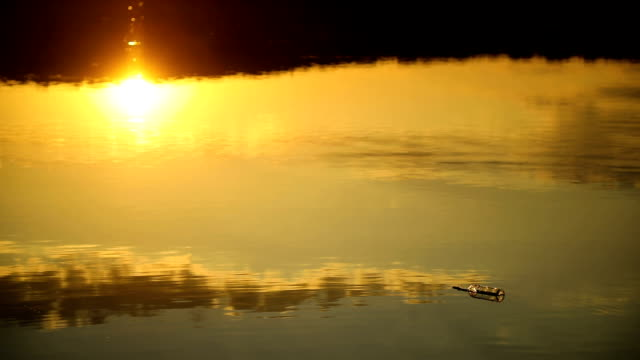 Message in bottle floating in the sea at beautiful sunset