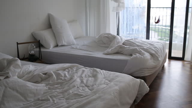 Messy Bedroom Messy double queen size bedroom in the morning. double bed stock videos & royalty-free footage