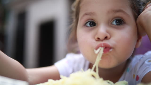 vidéos et rushes de fille enfant malpropre, manger des spaghettis à la maison - spaghetti bolognaise