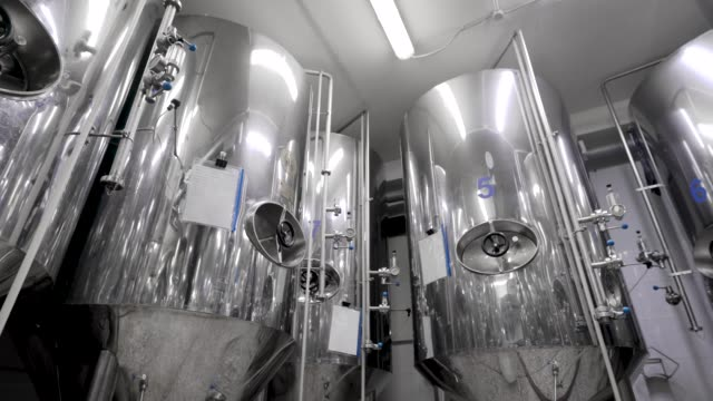 metal cisterns for mashing malt for beer are standing in shop of industrial brewery, round panoramic view - нержавеющая сталь стоковые видео и кадры b-roll
