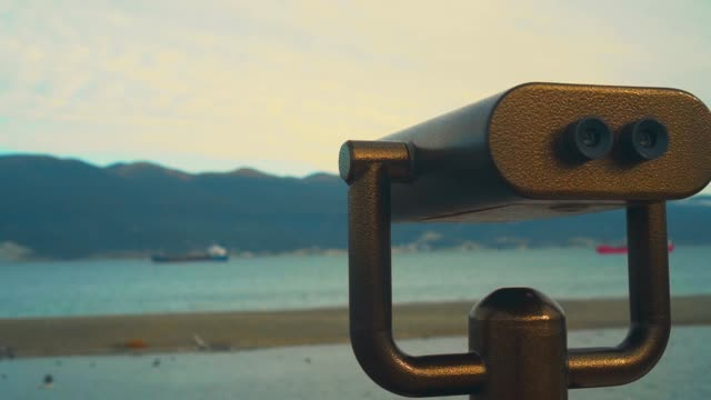 Metal coin operated gray telescope isolated on a view of a beautiful panoramic scenery, blue sky, sea water and mountains. Tourism concept.