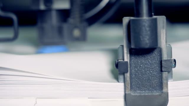 metal device splits paper at a print factory, close up. row paper sorting process. - мембрана клетки стоковые видео и кадры b-roll