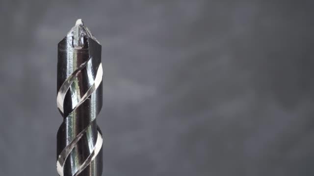 metal drill bit rotation on a dark background. macro view. - винт стоковые видео и кадры b-roll