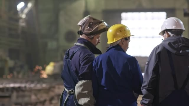 Metal Fabrication Plant Workers Walking through Facility Rear view of female engineer in hard hat walking through metal fabrication facility and discussing work with experienced male worker and young welder in safety uniform metal worker stock videos & royalty-free footage