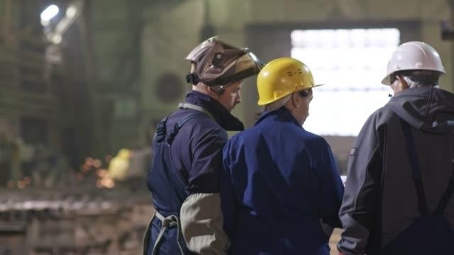 vídeos de stock e filmes b-roll de metal fabrication plant workers walking through facility - dureza