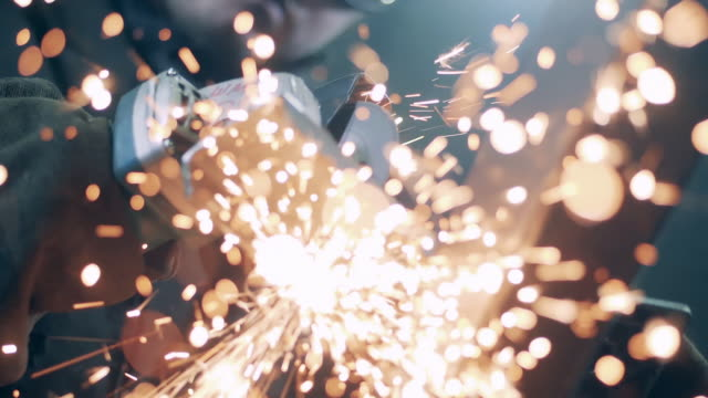 Metal is being cut and sparks are flying into the camera. Slow motion. video
