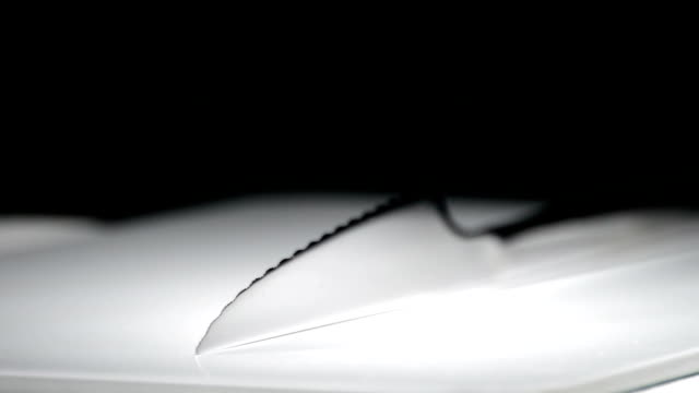 Metal knife rotating on white base with black background video