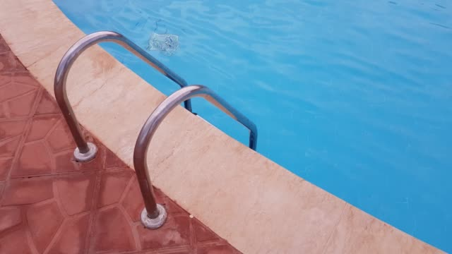 Metal ladder to the pool. in the pool is clear blue water. video