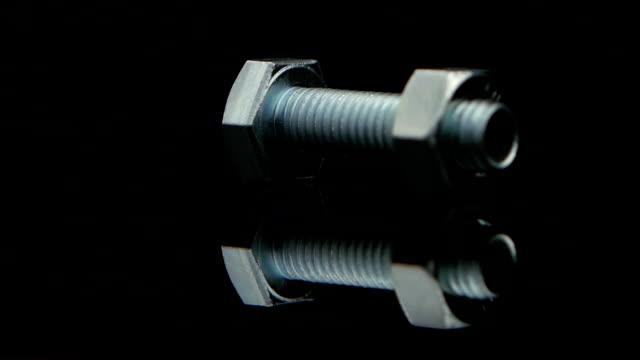 metal nut screwed on screw turn on black background studio - винт стоковые видео и кадры b-roll