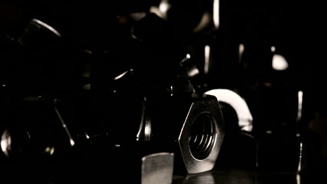 Metal nuts turn around in dark scene. video