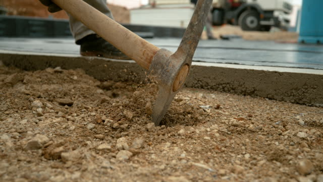 close up, dof: metal pickaxe strikes into the soft soil mixed with gravel. - ghiaia video stock e b–roll