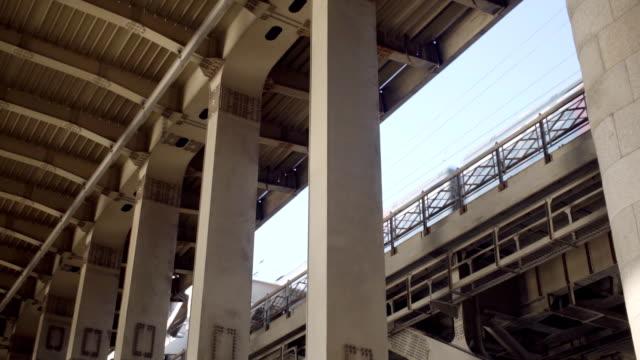 vídeos y material grabado en eventos de stock de pilares metálicos de la puente y el tren pasa en segundo plano - bajo posición descriptiva